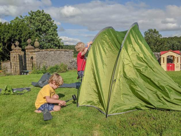 two boys erecting green tent