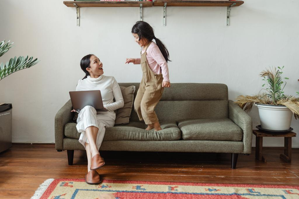 Woman working remotely and girl on sofa