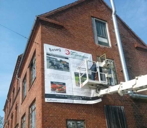 Det store banner for Fyens Væddeløbsbane er ved at blive monteret på gakven på ejendommen Vesterbro 116.