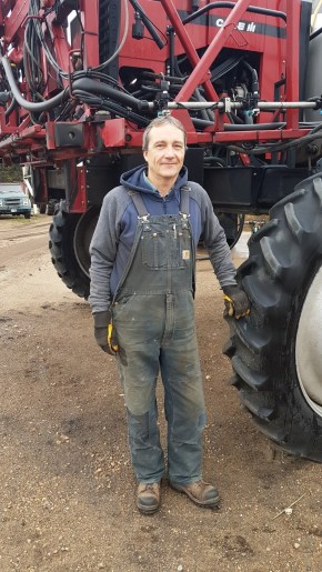 Brent Trawin leaning on a sprayer tire