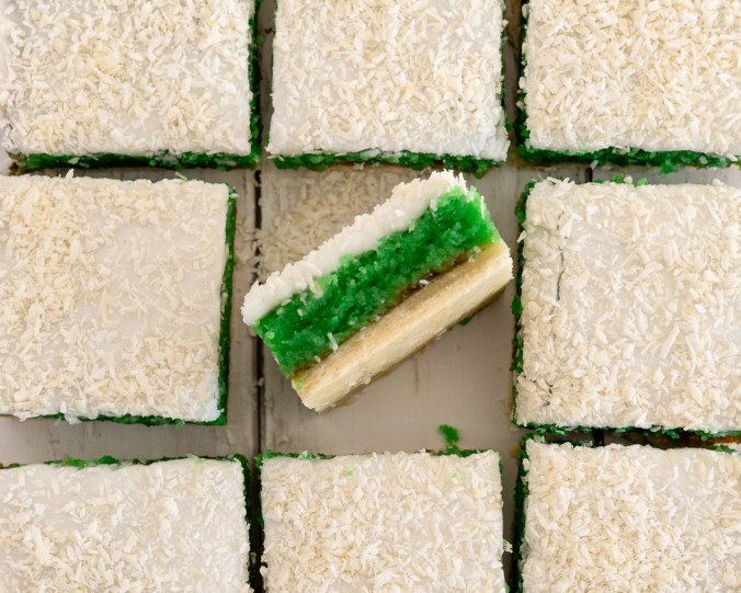 A Green Square traybake on it's side showing the green colored sponge and white icing