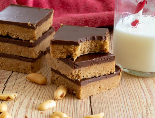 Two stacks of chocolate-topped peanut butter bars sitting beside a small bottle of milk with a red and white straw in it.