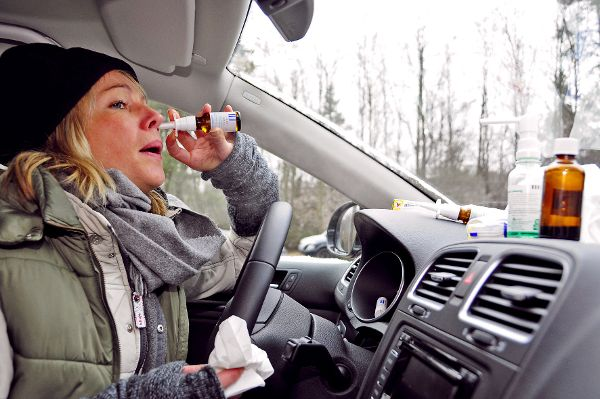 Frau im Auto nimmt Medikamente.