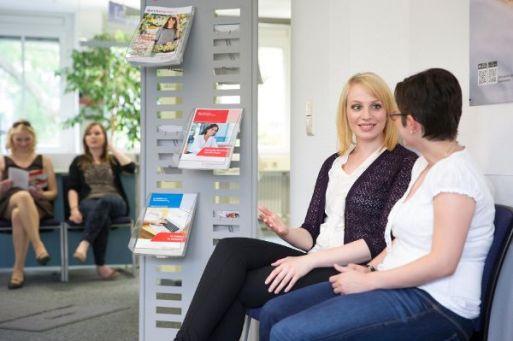 Zwei Personen warten vor einem Büro.
