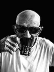 man in white crew neck shirt wearing black sunglasses holding black ceramic mug