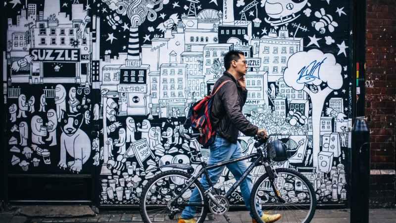 Mann schiebt Fahrrad vor einer Grafitti Wand