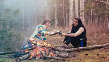 Zwei Frauen am Lagerfeuer.