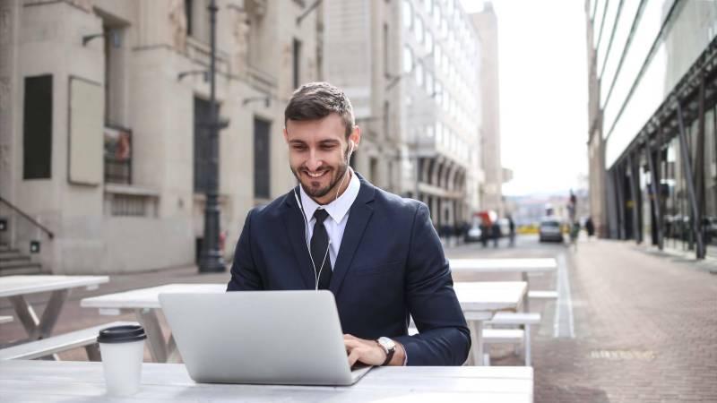 Mann mit Schreibtisch und PC sitzt auf der Straße