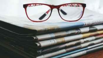 Brille auf Zeitungen.