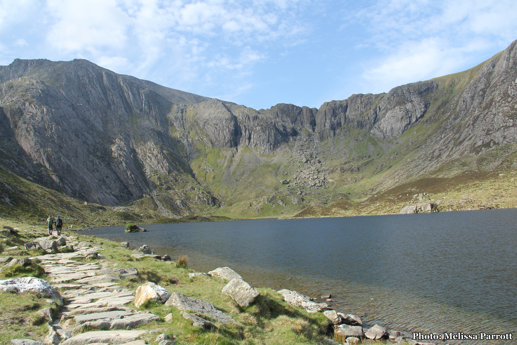 They pointed to a diverging path ahead, near a boulder and said that would take me over the adjacent mountain, down a valley to the lake below Tryfan, but it would take probably 6 hours to traverse and usually they start from the other side (Northern entrance). The lake was bright blue, reflected from the nearly cloudless sky.