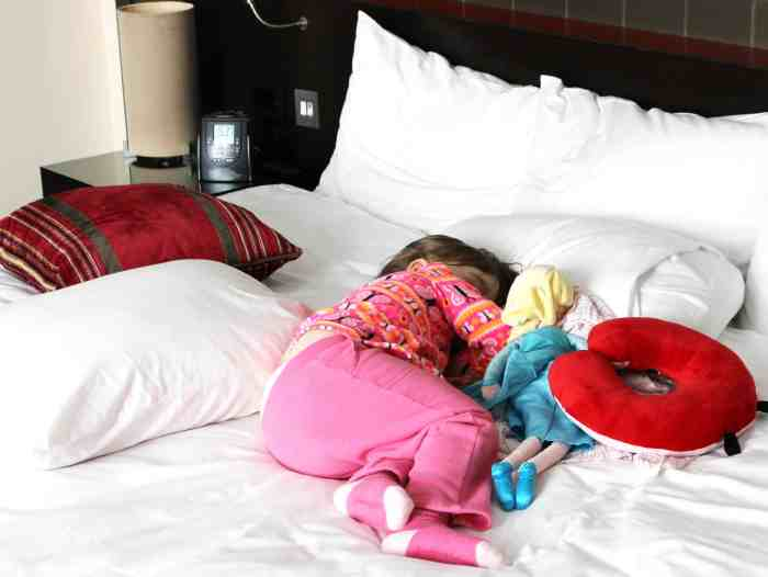 Little girl taking a nap on a bed surrounded by pillows