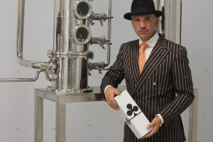 David Lee Meisenburg standing in front of distilling equipment.