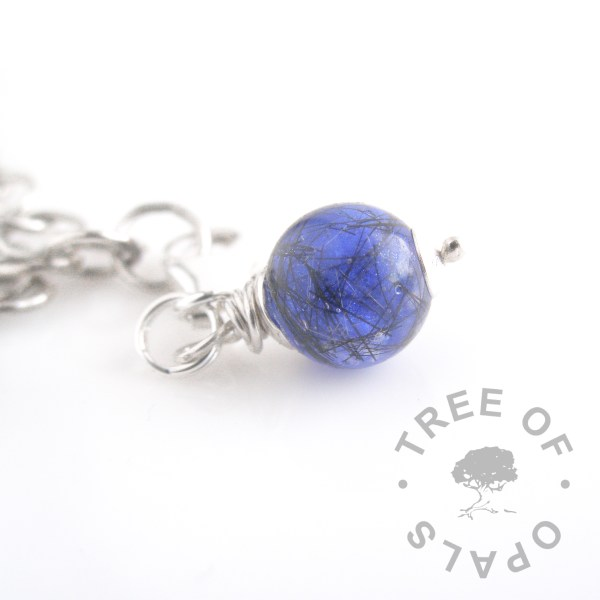 lock of hair pearl lobster claw dangle charm with blue shimmer powder showing short hair which is placed round the edge of the pearl before the colour is added for visibility
