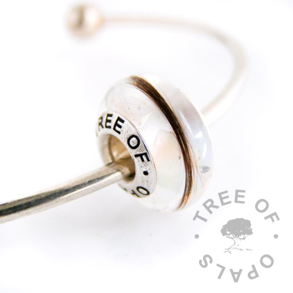 lock of hair charm with real opal flakes on a sterling silver torque charm bangle