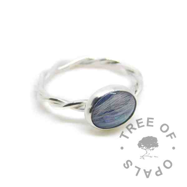 lock of hair memorial ring with Aegean blue resin sparkle mix. Solid sterling EcoSilver handmade setting with twisted wire band style. 10x8mm cabochon (stone) pet fur ring. White/grey hair visible in resin.