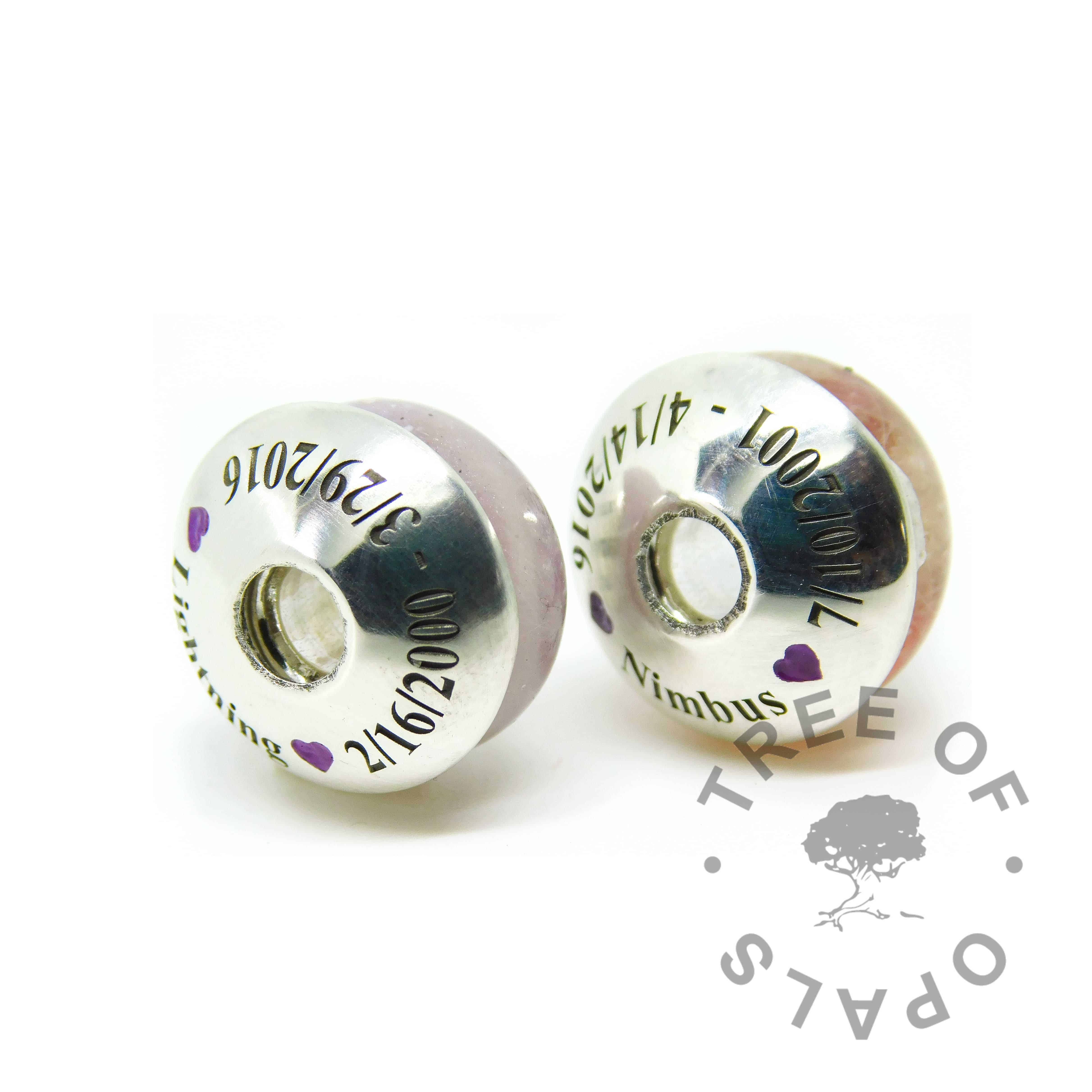 fur ash charm duo with engraved charm washers in Times New Roman font, two dates, names and hearts with purple cold enamel in the hearts. Handmade shapes. Watermarked copyright image by Tree of Opals