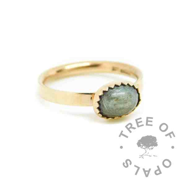 14ct gold fur ring with mermaid teal resin sparkle mix, no birthstone. Brushed ring band handformed with solid 14ct gold, and 8x6mm serrated bezel cup. Hallmarked with Tree of Opals maker's mark at The Birmingham Assay Office. Watermarked copyright Tree of Opals memorial jewellery imageq