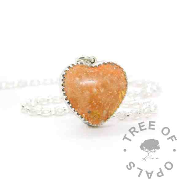 New style heart necklace setting with scalloped edge. Tangerine orange resin sparkle mix, cremation ashes, shown with a medium classic chain upgrade (mockup of new setting)