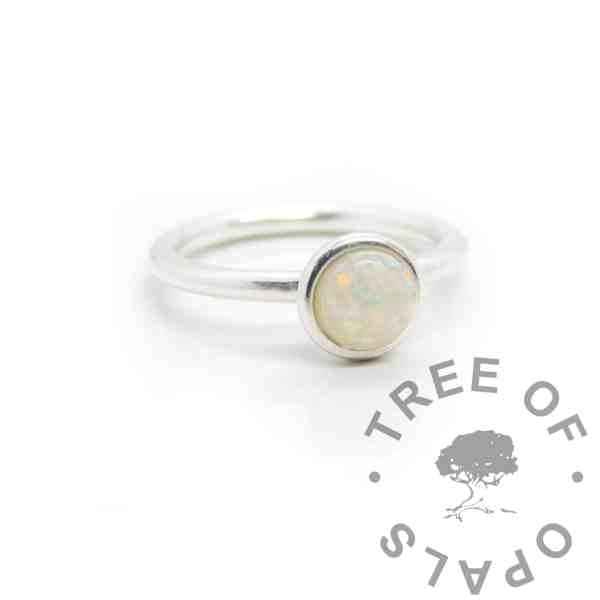 Opal breastmilk Ayla Solitaire Ring, preserved dried breastmilk in resin with synthetic opal pieces made into a cabochon (stone) and set into the ring with glue. Opal represents the five year breastfeeding award and also the October birthstone. Cast Argentium 935 anti-tarnish silver (higher purity than sterling)