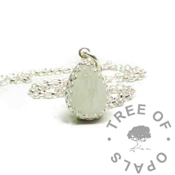 breastmilk teardrop necklace mockup, breastmilk with unicorn white sparkle mix in 14x10mm teardrop crown point setting. Shown with a classic chain
