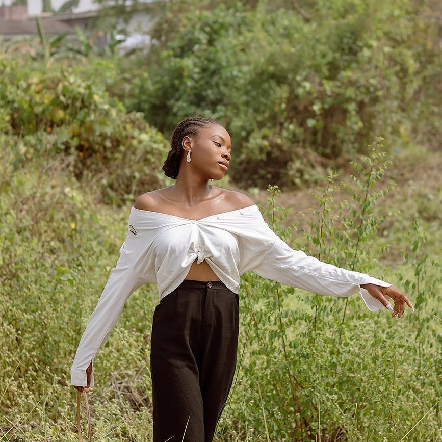 black woman in trendy outfit on grassy meadow near shrubs