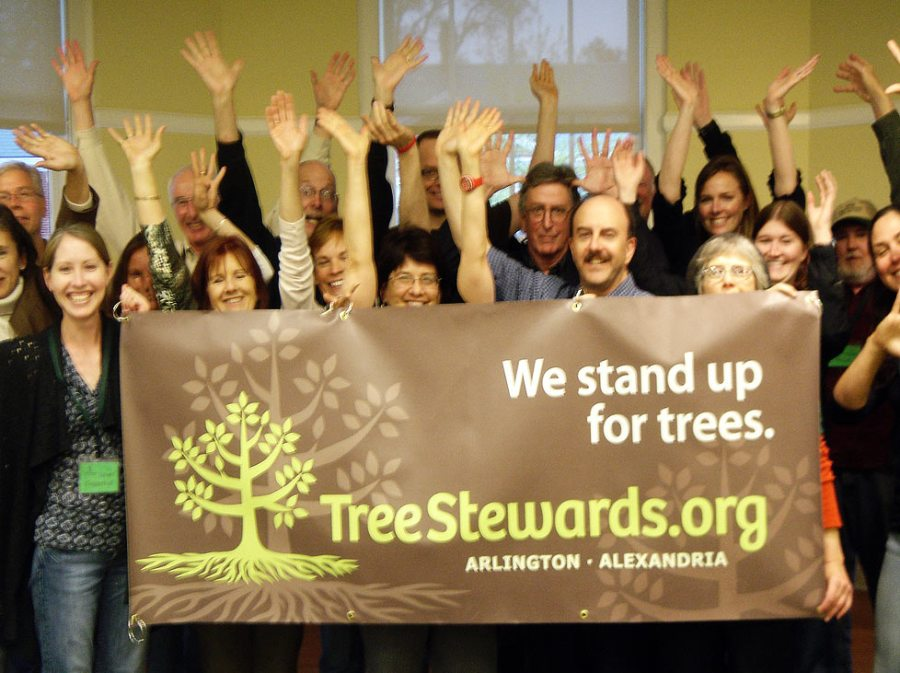 TreeStewards graduates pose with the banner, We Stand Up for Trees!