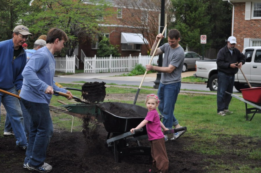 Little girls helps adults with mulching