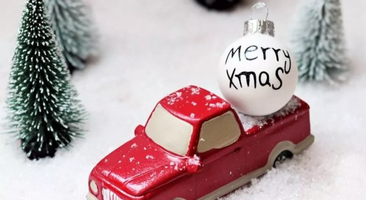 Red truck with Christmas Ornament by fir trees in snow