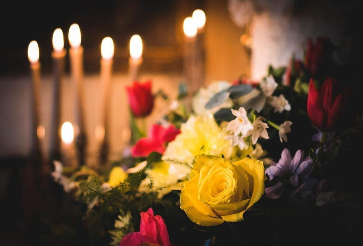 A 17th Century Style Bouquet set on a table with lit candles in the background