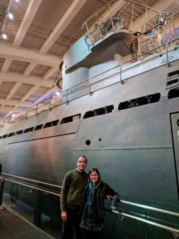 Man and woman standing next to WWII submarine in museum