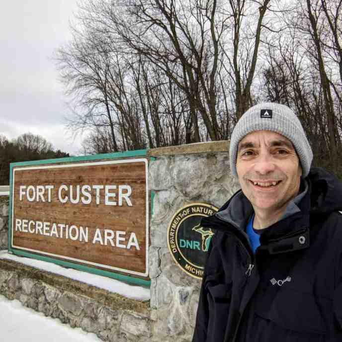 man and sign for Fort Custer Recreation Area