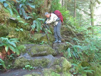 Lori climbing down a little stretch of rock to see Chinook Falls.
