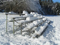 Snow covered bleachers. Looks like someone has been using them.