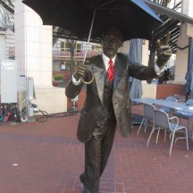 Often used for a selfie. He didn't use to have a red tie or white shirt but I guess they dress him up more. Located in Pioneer Court House Square.