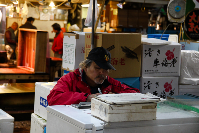 A shopkeeper tallies the morning's sales