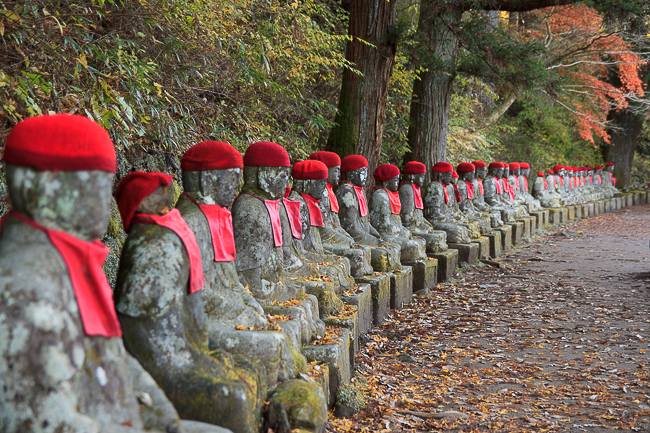 A seemingly endless row of guardians line the path at Kanmangafuchi