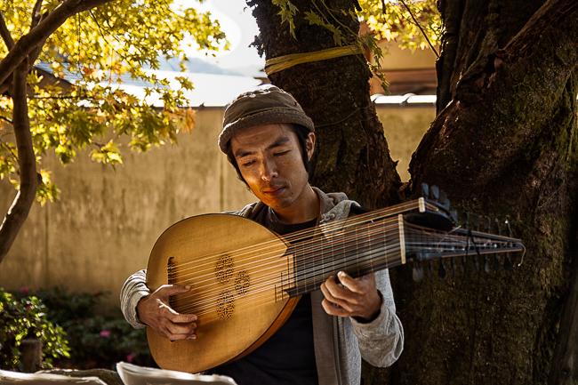 A musician plays a guitar like Biwa on the path
