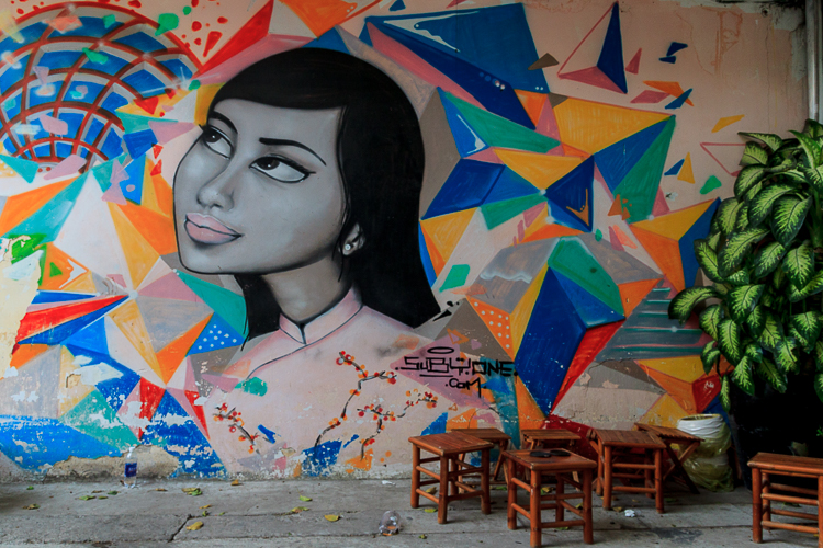 A large mural by a small hip cafe