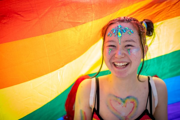 A young person standing underneath a rainbow flag with gems on their face, image provided by BeLonG To and Dublin Bus campaign