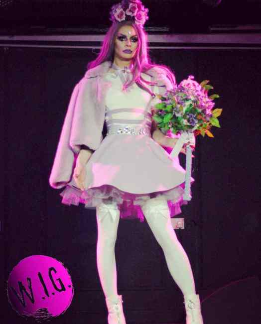 Annie Queeries holding a floral bouquet and wearing a pastel purple dress, reigning ruler of Haus of W.I.G