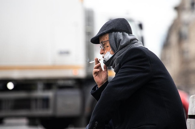 Man with mask smoking  cigarette