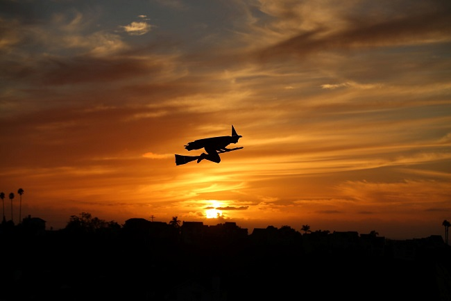A remote-controlled plane in the form of a witch flies over a neighborhood as the sun sets during Halloween in Encinitas