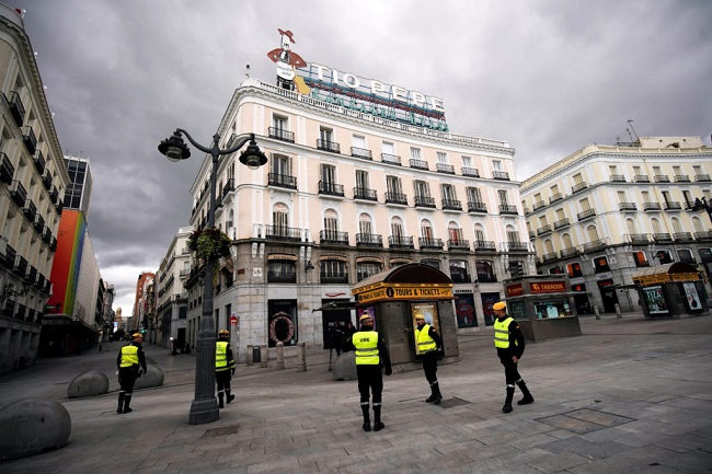 Members of the Military Emergency Unit (UME) patrol in an almost empty Puerta del Sol square during partial lockdown as part of a 15-day state of emergency to combat the coronavirus disease outbreak in Madrid