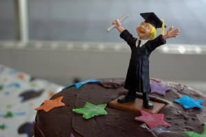 Picture of a figurine of a graduate student in cap and gown on top of a cake.