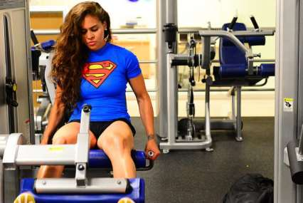 A beautiful woman wearing black t-shirt and black shorts working out in gym
