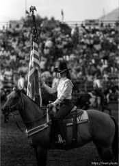 Flag and rider on horse to open rodeo.