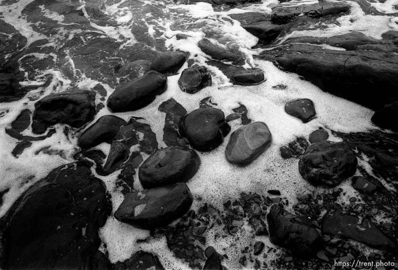 rocks and surf at beach.