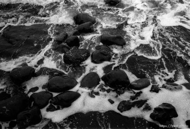 black rocks and surf at beach.