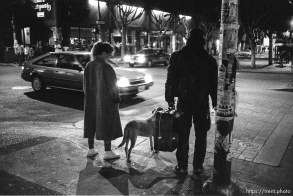 Man with suitcase and woman with dog on Telegraph Avenue at night.