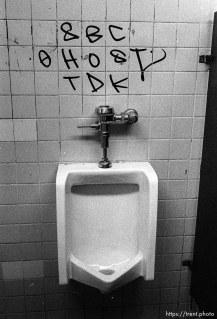 Graffiti over a urinal.